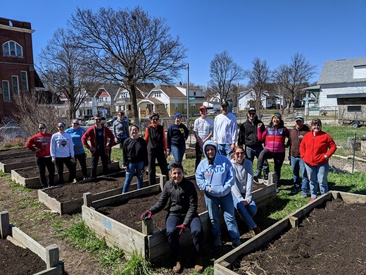 Good City volunteers pose in front of raised beds at the Victory Garden Initiative's urban farm in Harambee.